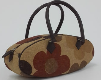 Brown floral printed canvas oval shape bag, top handle bag.