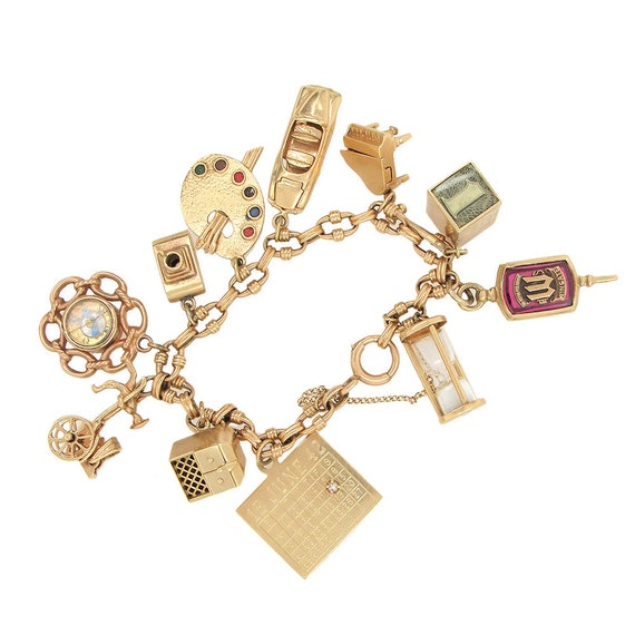 14K gold charms bracelet with 11 charms, circa 195