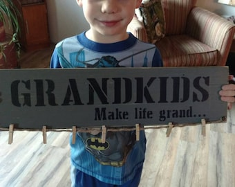 Grandkids make life grand pallet sign with clothespins for pictures.