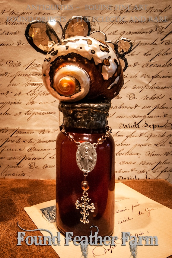 Handmade Glass Cross Bottle with an 1890's era Antique Amber Glass Bottle Base with a Polished Sarmaticus Turbo Shell