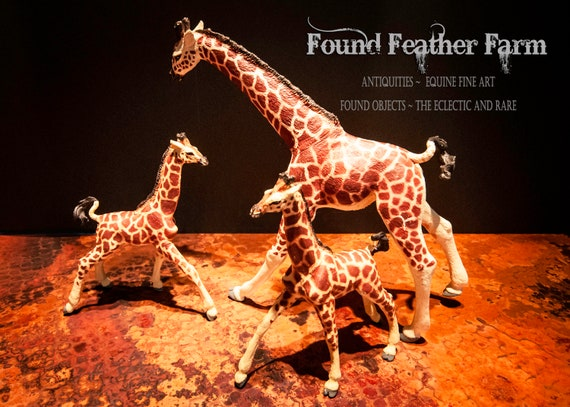 A Resin Toy Figurine of a Giraffe Mother and Her Twin Babies