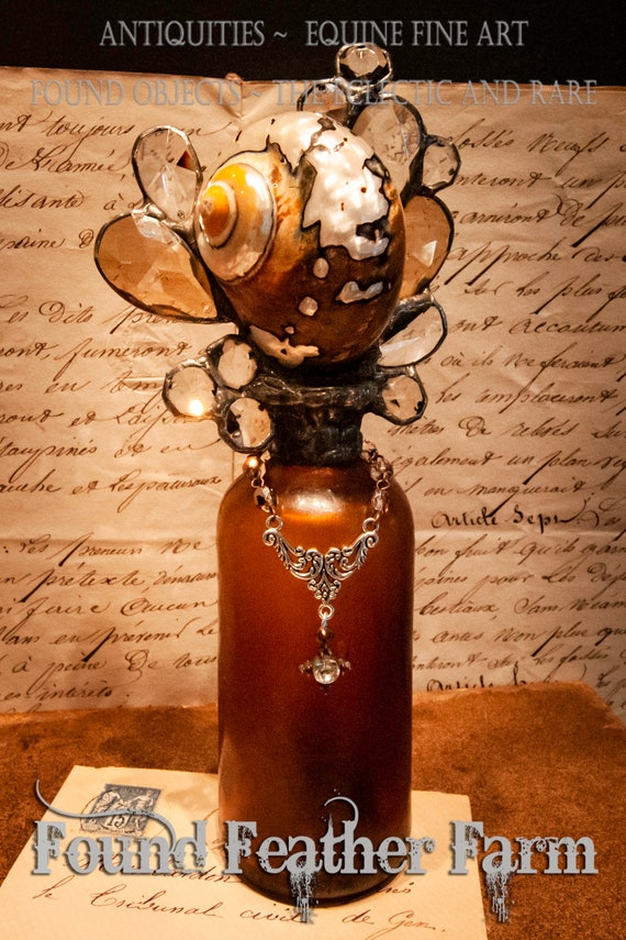 Handmade Glass Cross Bottle with an 1890's era Antique Amber Glass Bottle Base and a Polished Sarmaticus Turbo Shell