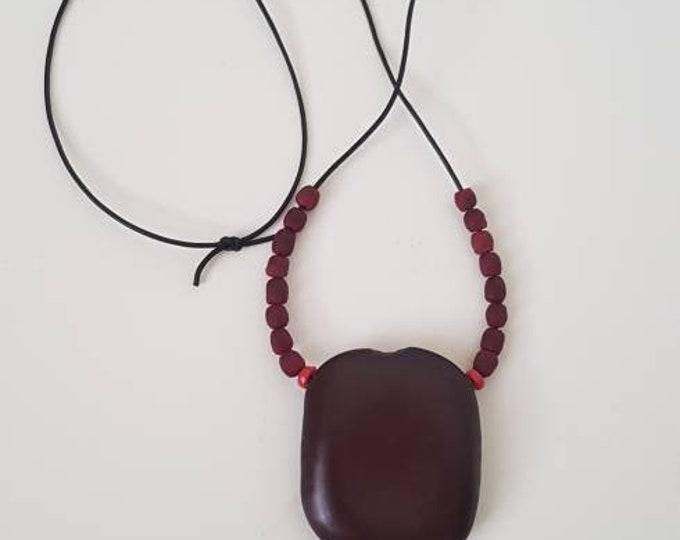 Recycled beads necklace. Black leather string. Red recycled glassbeads from Ghana. Organic seed from Benin. Handmade in Denmark.