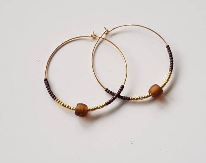 Golden earrings hoops on real silver material. Brown recycled glass bead from Ghana. Jewellery handmade in Denmark.