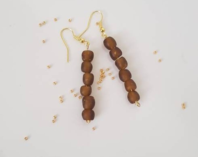 Golden earrings on real silver material. Brown recycled glass beads from Ghana. Jewelry handmade in Denmark.