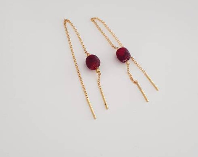 Golden earrings on real silver material. Red recycled glass beads from Ghana. Jewellery handmade in Denmark.