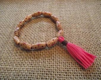 Patterned wood bead bracelet with pink tassel