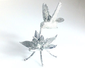 Hummingbird on Columbine Flower, each is  life size, sculpted and cast by Don Norris with lead free pewter in Tucson, Arizona.