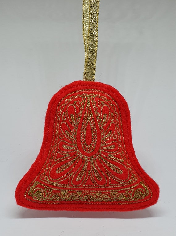 X059.      The gold Christmas bell on red felt