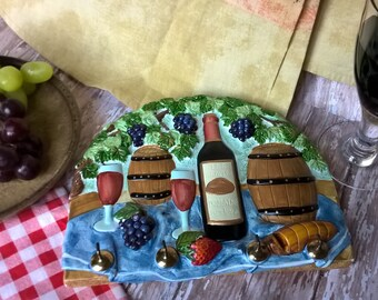 Chalkware kitchen plaque of French wine, grapes, bread and fruit. With hooks for keys or tea towels.