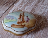 Porcelain trinket box lid decorated with C17th or early C18th settler coming ashore from sailing ship. Exotic fruits decorate the box .