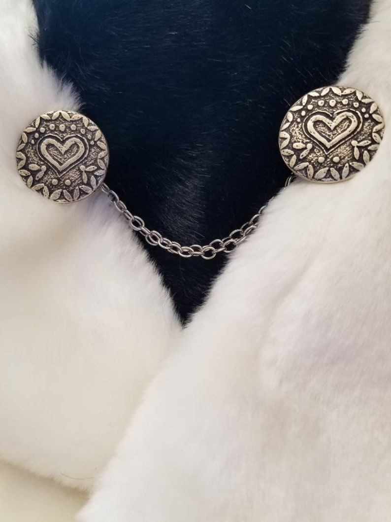color- silverblack size is approximately half dollar Cloak clasps