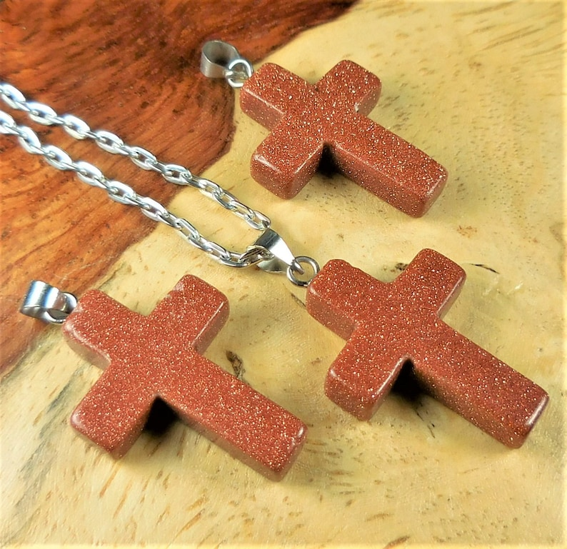 Carved Goldstone cross on cotton cord
