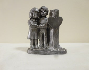 Pewter sculpture of two young people in love next to a heart