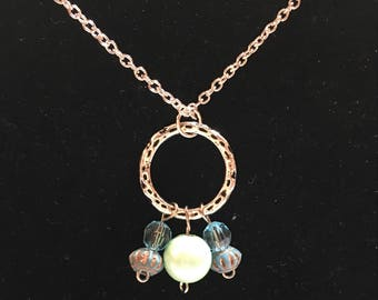 Silver chain and hammered silver circle pendant with beaded charms in various shades of green