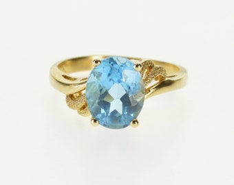 10k Oval Blue Topaz Solitaire Textured Wave Accent Ring Gold