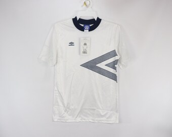 815efc26a69 90s New Umbro Mens Small Spell Out Azteca Short Sleeve Soccer Jersey White