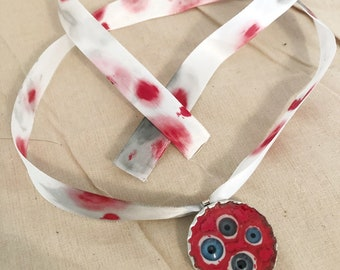 creepy doll eyes necklace charm on blood stained ribbon blue eyes horror halloween weird christiecreepydolls