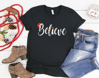 Christmas Tshirt Believe in Santa with Santa Hat | Unisex Short Sleeve Tshirt | Teacher Holiday Shirt