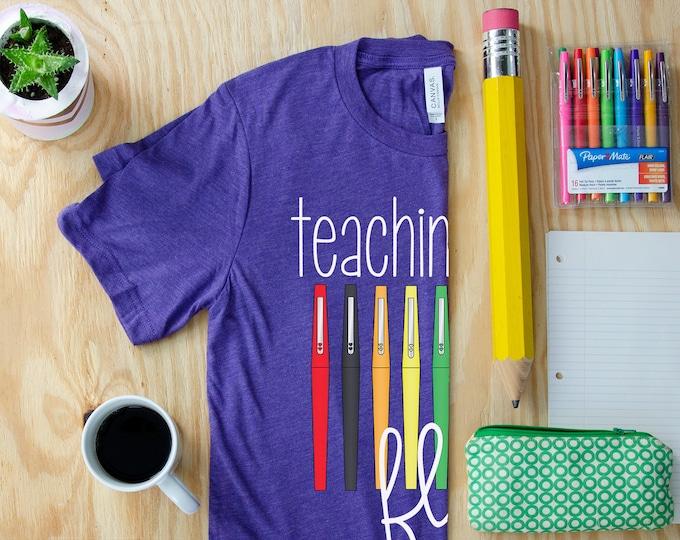 Teaching with Flair Unisex Teacher T-shirt | First Grade Kindergarten Level Shirt | Elementary Teacher Shirt Pens