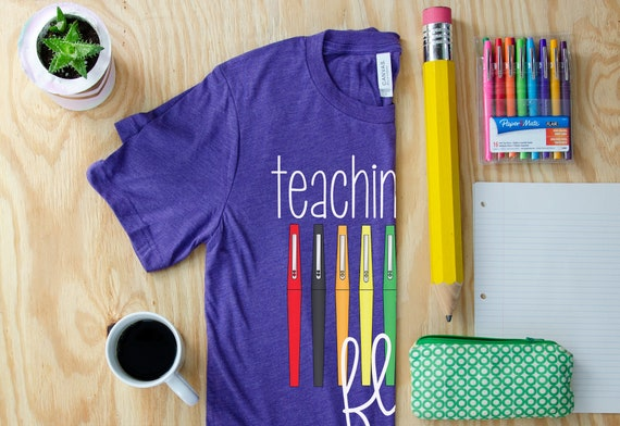 Teaching with Flair Unisex Teacher T-shirt | First Grade Kindergarten Level Shirt | Elementary Teacher Shirt Pens
