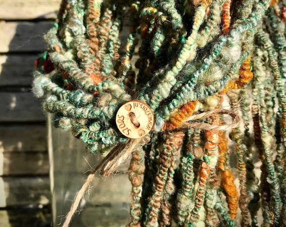 Hand spun beaded art yarn inspired by the '70s. Supercoils, large glass beads and lots of green, brown and orange.