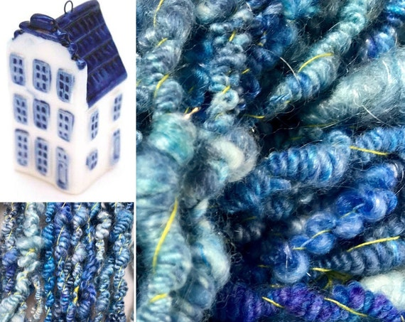 Hand spun supercoil art yarn in royal Delft blue with a vibrant yellow autowrap thread. Made out of Merino wool, silk en faux angora.