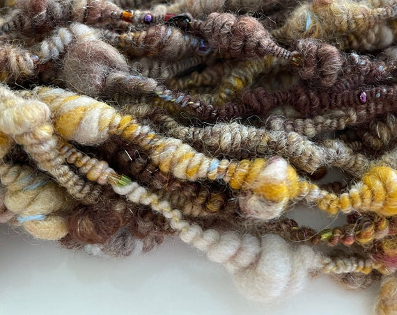 Brown and yellow beaded handspun art yarn. Made out of soft Merino wool, sari silk, silk, Alpaca, a string of beads and a dash of glitter.