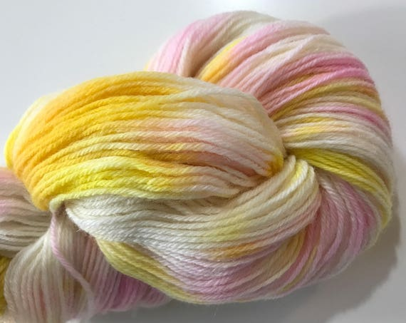 Hand dyed fine wool yarn in pink, yellow and white.