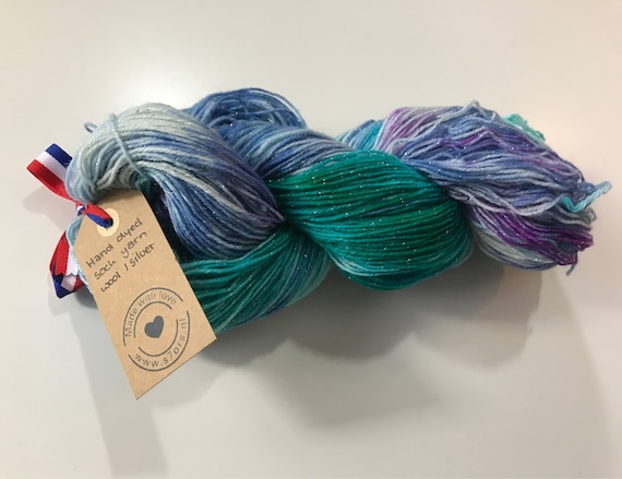 Hand dyed Merino sock yarn with a string of silver polyamide. Dyed in the colours of the ocean.