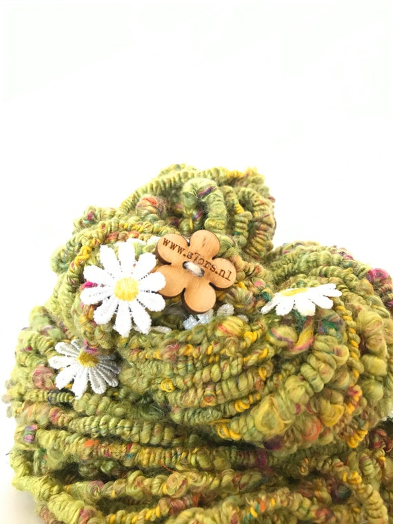 Hand spun art yarn in supercoils with embroidered daisies. Fine merino, silk and Finnish cotton thread.