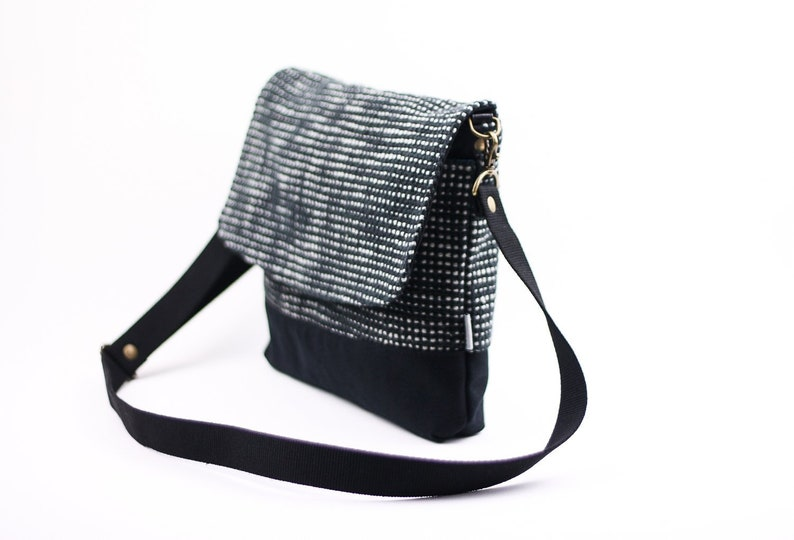 b30c19a1b8c Black and white messenger crossbody bag with pockets and adjustable strap.  Black vegan crossover purse