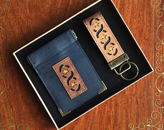 Boxed set of coin purse and key ring made from navy blue vegan cork leather with a mid-brown ribbon and star appliqué and squeezy closure