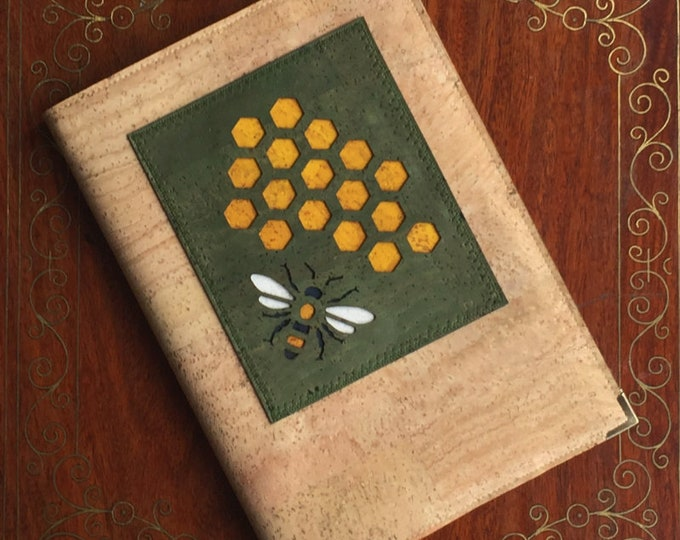Vegan A5 notebook made from beige cork leather/fabric with an olive green appliqué of a bee and honeycomb backed in coloured cork