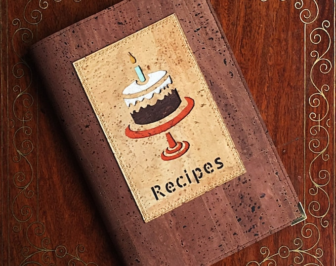 Vegan A5 recipe book/baking book made from mid brown cork leather/cork fabric with an appliqué of a birthday cake backed in coloured cork
