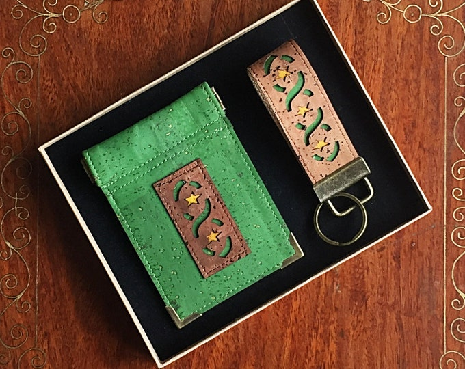 Boxed set of coin purse and key ring made from forest green vegan cork leather with a mid-brown ribbon and star appliqué and squeezy closure