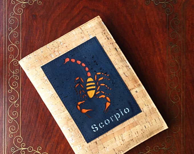 Silver flecked natural fawn cork leather covered plain paper notebook with a laser cut applique of the Zodiac sign Scorpio in navy cork