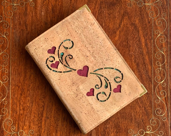 A6 notebook covered in beige cork fabric/cork leather  -  laser cut design of hearts and tendrils backed with red and green cork