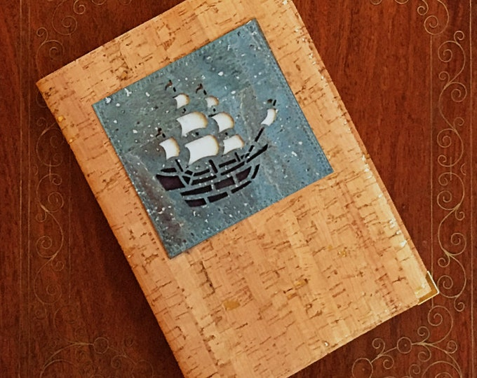 A galleon in full sail on a silver flecked blue background enhances an A5 beige cork leather/cork fabric notebook - vegan friendly