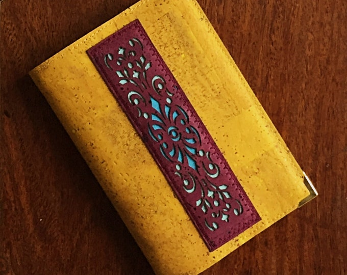 A6 mustard yellow vegan cork leather notebook embellished with a dark red cork appliqué and a geometric design backed with coloured cork