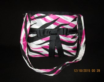 Pink, black, and grey zebra print purse with a black ribbon and bow