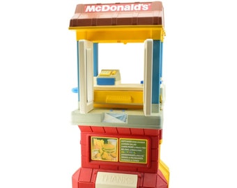 Vintage (1989) Fisher Price McDonald's Drive Thru Playset on wheels with accessories.