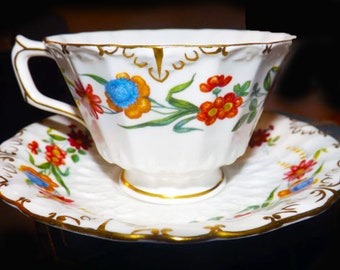 Vintage (1960s) Royal Crown Derby Chatsworth A798 hand-decorated cup with matching saucer. Multicolor florals, fluted body, gold edge.