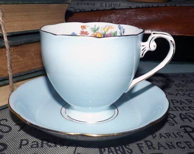 Mid-century (1950s) Royal Grafton harlequin-style tea set (footed cup with saucer). Pale blue body, multicolor florals, gold edge, accents.