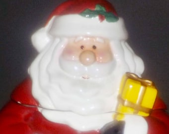 Vintage ceramic Santa Claus Christmas cookie jar.  Santa in his red suit and black boots with a candy cane in one hand, presents in other.