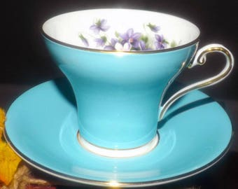 Mid-century John Aynsley hand-decorated tea set (corset cup with saucer) made in England. Teal with violets, gold edge, accents.