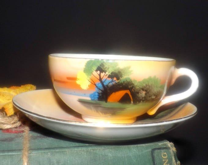 Early mid-century (1940s) Noritake Chikaramachi   Nippon hand-painted lusterware tea set (flat cup with saucer). Orange sky, trees, cabin.