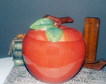 Vintage (early 1990s) large, figural cookie jar with lid in the shape of a juicy, red apple. Greenery, majolica branch lid.