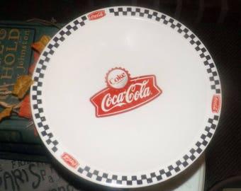 Gibson Coca-Cola Town Square pattern rimmed salad | side plate.  Black checkerboard edge, coke cap logo, red Coke banner. Retired 2004.