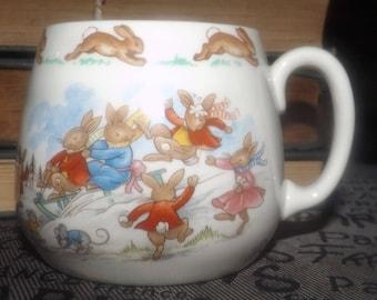 Vintage (1980s) Royal Doulton Bunnykins baby | child | toddler cup | mug. The bunnies enjoy winter fun on a sled, snowballs, snowman.